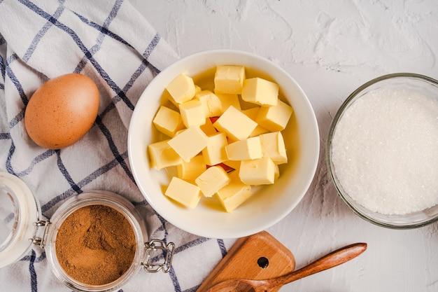 Keukengerei en bakselingrediënten voor cupcakes op witte steenachtergrond