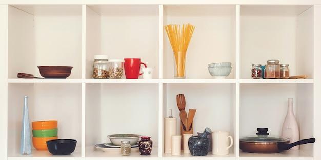 Keukengerei en servies op witte planken. goed georganiseerd keukenconcept. moderne interieur. open kast met schone gerechten. open planken in de keuken.