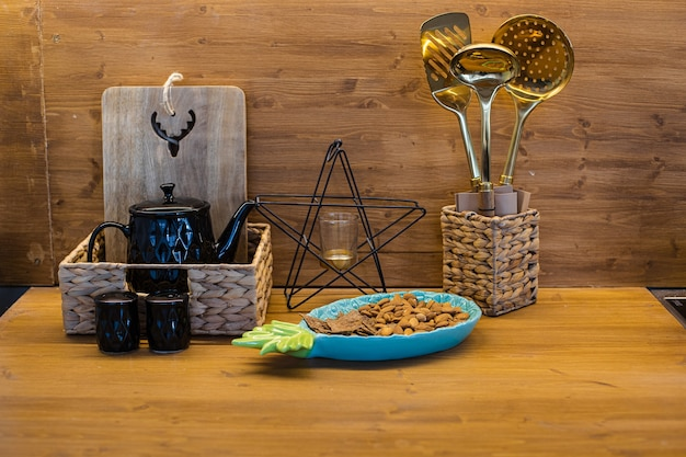 Keukengerei, gereedschap, decoratieve elementen en amandelnoten met gezonde crackers op blauwe schotel in de vorm van ananas op houten aanrecht of tafel.