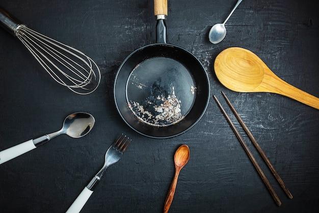 Keukengerei op zwarte achtergrond wordt geplaatst die