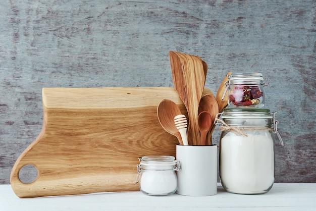 Keukengereiachtergrond met een houten snijdende raad, het concept van de huiskeuken