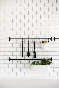 Keukengereihanger op witte bakstenen muur