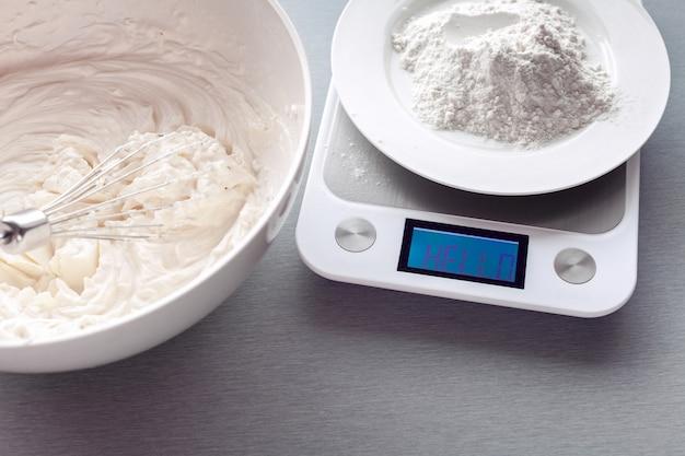 Keukengewichten meten de massa van meel voor het maken van koekjes