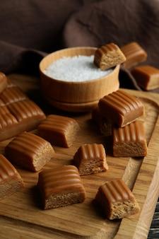 Keukenhanddoek en bord met karamelstukjes en zout op houten tafel