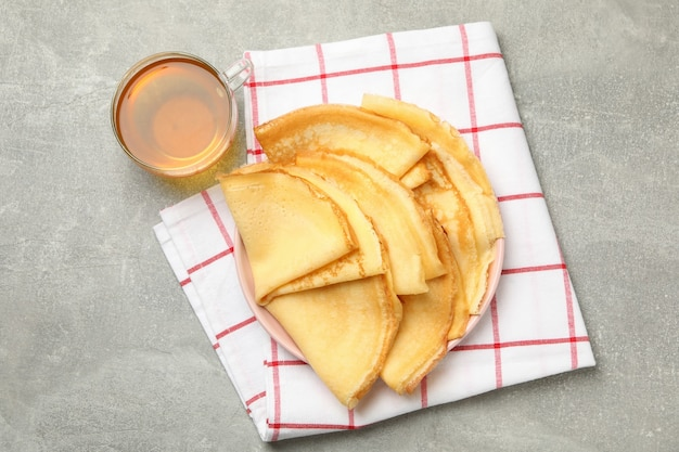 Keukenhanddoek met plaat van dunne pannenkoeken en thee op grijze tafel