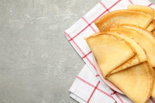 Keukenhanddoek met plaat van dunne pannenkoeken op grijze tafel