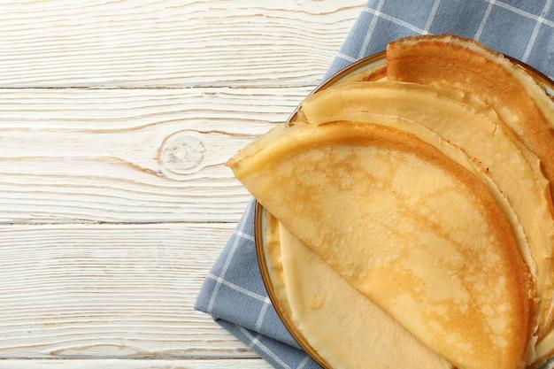 Keukenhanddoek met plaat van dunne pannenkoeken op houten achtergrond