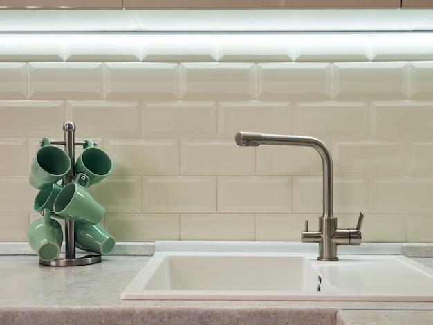 Keukenkraan en standaard met groene mokken bekers op de achtergrond van een witte betegelde muur in de keuken