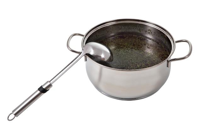 Keukenlepel van metaal dat op pot soep wordt geleund, die op wit wordt geïsoleerd.