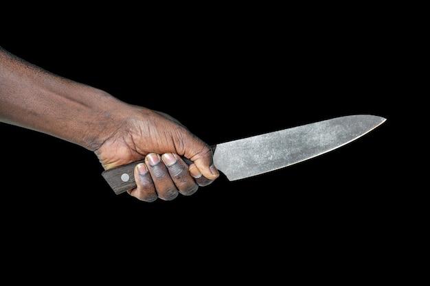 Keukenmes in een hand. groot keukenmes in afrikaanse mensenhand dat op een zwarte wordt geïsoleerd
