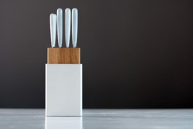 Keukenmes in witte houder op de witte tafel
