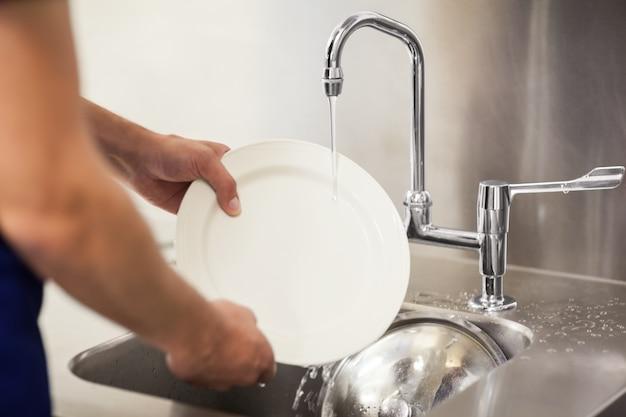 Keukenportier die witte platen in gootsteen schoonmaken