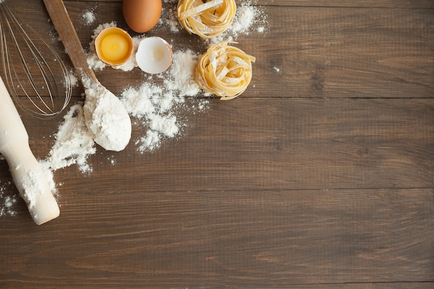 Keukensamenstelling met fettuccine gebarsten eieren, keukengerei, bloem. uitzicht van boven.