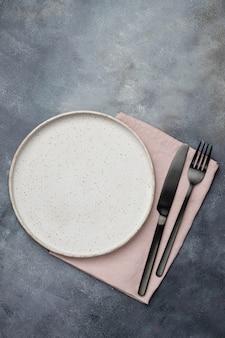 Keukentafel met lege beidge keramische plaat en zwarte vork en mes