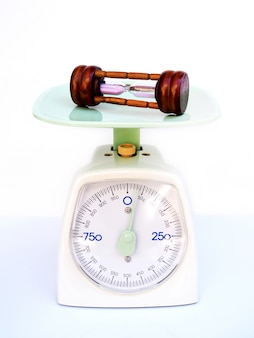 Keukenweegschaal of weegschaal en zandloper, concepttiming om gewicht te verliezen en zorg te dragen voor de gezondheid.