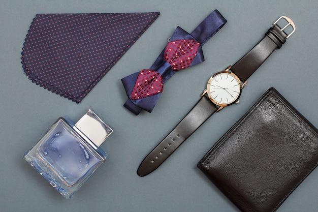 Keulen voor mannen, zakdoek, vlinderdas, horloge met een zwart lederen band en lederen tas op grijze achtergrond. accessoires voor heren. bovenaanzicht