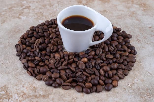 Keurig geordende stapel koffiebonen rondom een kopje koffie