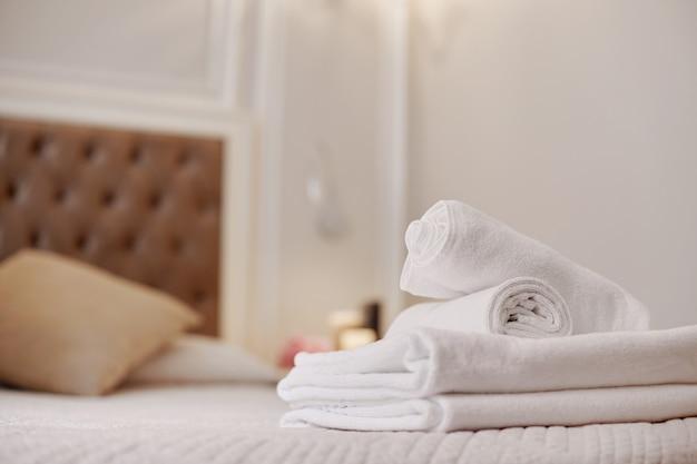 Keurig opgevouwen witte handdoeken liggen op het bed in de kamer