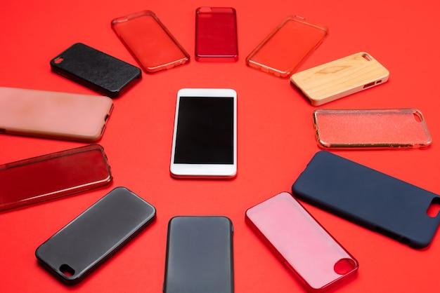 Keuze uit veelkleurige plastic achtercovers voor mobiele telefoons op rode achtergrond met een smartphone aan de zijkant
