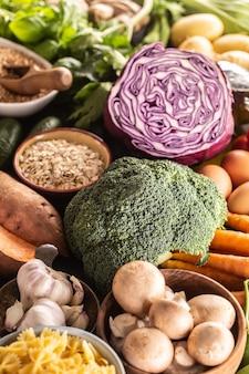 Keuze uit vers voedsel en gezond eten gericht op broccoli. groenten, fruit, peulvruchten en granen op een betonnen tafel.