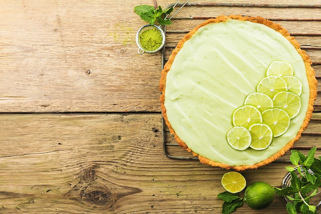 Key lime pie met verschillende limoenen en munt op houten oppervlak, bovenaanzicht met kopie ruimte.