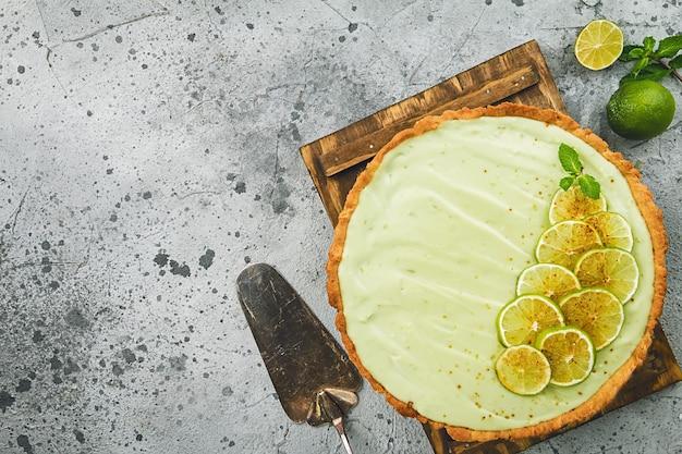 Key lime pie met verschillende limoenen en munt over grijs oppervlak, bovenaanzicht met kopie ruimte.