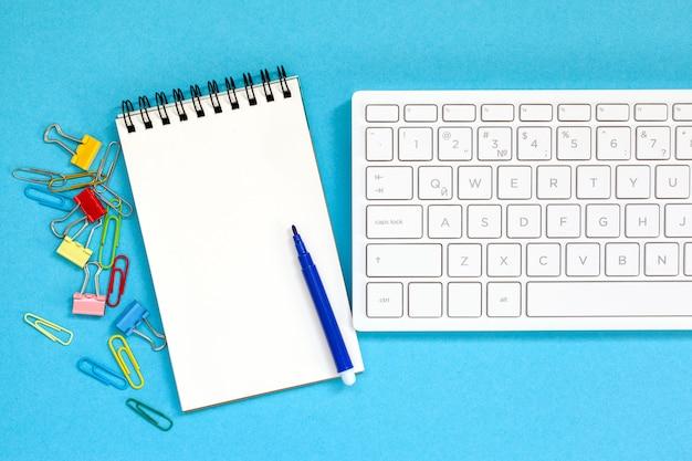 Keybord met lege spiraal notebook, pen op blauw