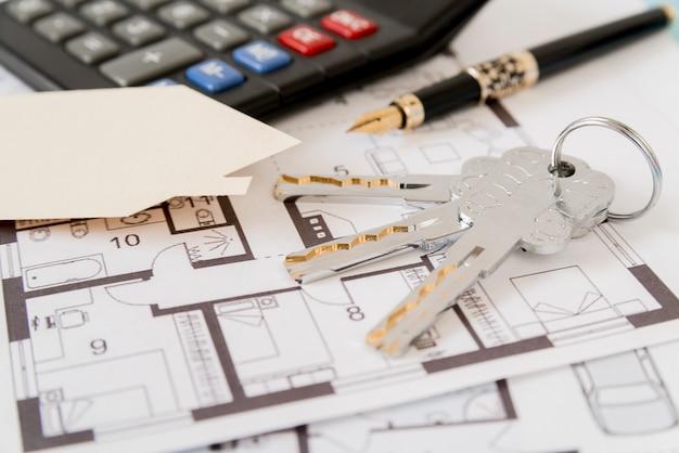 Keys; vulpen; huis papier uitgesneden en rekenmachine op architecturale blauwdrukken