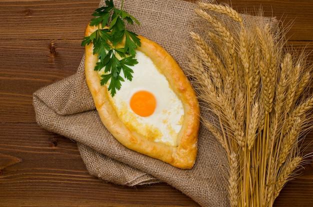 Khachapuri met ei en tarwe oren op plundering, donkere houten tafel