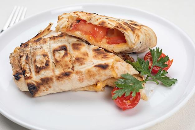 Khachapuri met kaas en tomaten op een witte plaat