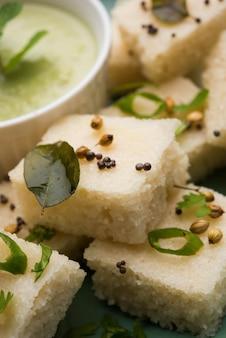 Khaman witte dhokla bestaande uit rijst of urad dal is een populair ontbijt- of snackrecept uit gujarat, india, geserveerd met groene chutney en hete thee. selectieve focus