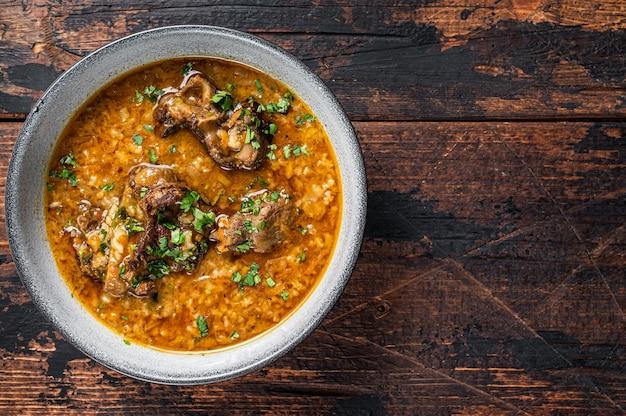 Kharcho-rundvleessoep met rijst, tomaten en kruiden in een kom. donkere houten achtergrond. bovenaanzicht. ruimte kopiëren.