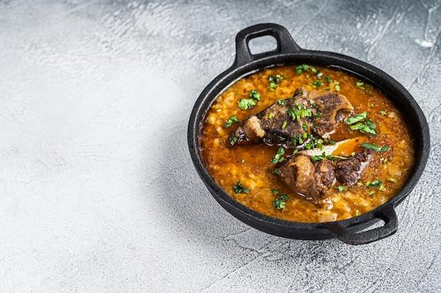 Kharchosoep met rundvlees, rijst, tomaten en kruiden in een pan. witte achtergrond. bovenaanzicht. ruimte kopiëren.