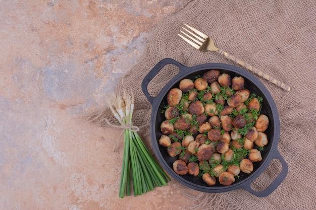 Khinkal-vullingen koken in een zwarte pan met kruiden en specerijen.
