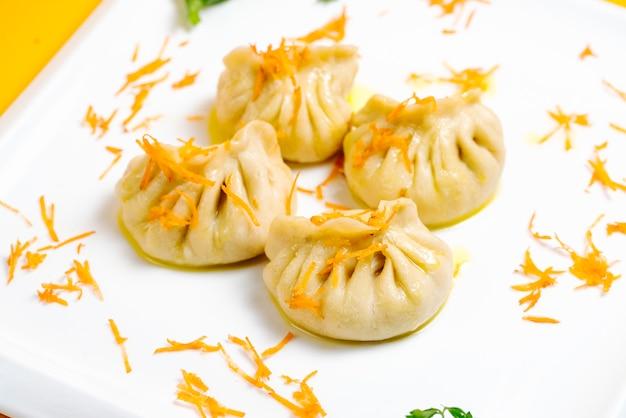 Khinkali gegarneerd met wortelchips