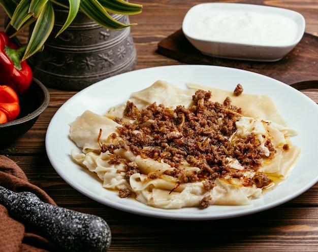 Khinkali in de vorm van bladeren met gevulde vlees en gebakken uien op tafel