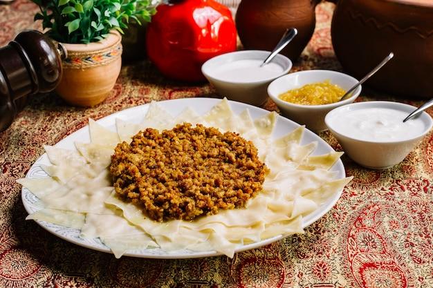 Khinkali met het knoflook zijaanzicht van vlees duidelijk youghurt ui