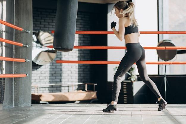 Kickboksende vrouw in airpods die bokszak in het sterke lichaam van de geschiktheidsstudio woeste sterkte opleiden