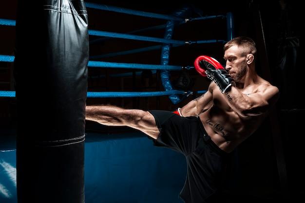 Kickboxer trapt de tas. een professionele atleet trainen. het concept van mma, worstelen, muay thai. gemengde media