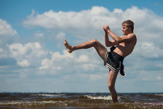 Kickboxer trapt in de open lucht in de zomer tegen de zee.