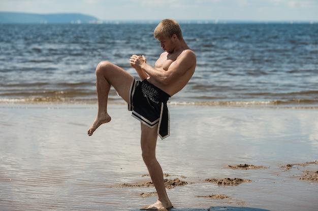 Kickboxer trapt in de zomer de open lucht tegen de zee in.