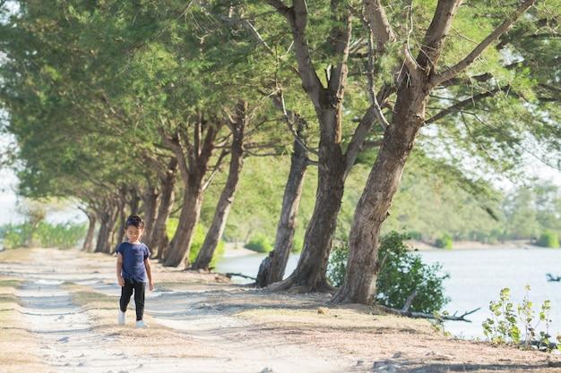 Kid alleen lopen tussen bomen