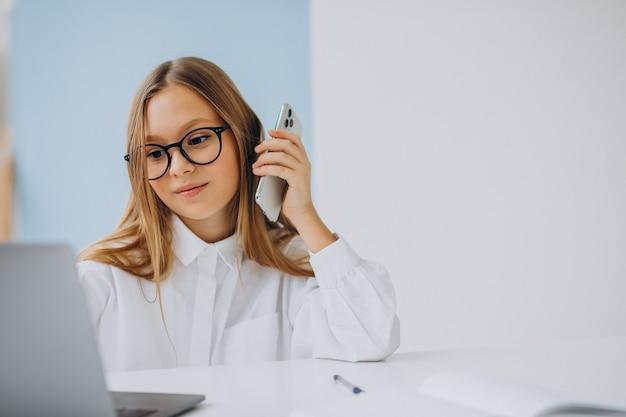 Kid baas met behulp van laptop en praten aan de telefoon