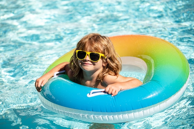 Kid bij aquapark kids zomervakantie jongen in zwembad gelukkige jongen op opblaasbare rubberen cirkel