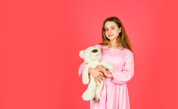 Kid bij speelgoedwinkel. zorgeloos en gezellig voelen. klein meisje houdt teddybeer vast. retro meisjesspel met beerstuk speelgoed. gelukkige jeugd. cadeau voor verjaardag vakantie. beste cadeau ooit. valentijnsdag. ruimte kopiëren.