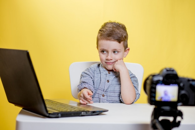 Kid blogger filmt video op camera die met de laptop werkt, thuis. online leren. online school.