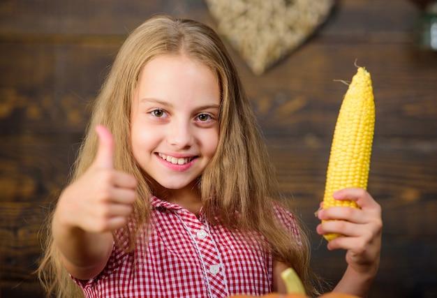 Kid boer met oogst houten achtergrond. oogstfeest concept. meisje kind op boerderijmarkt met biologische groenten. kind meisje geniet van het boerenleven. biologisch tuinieren. kweek je eigen biologische voeding.