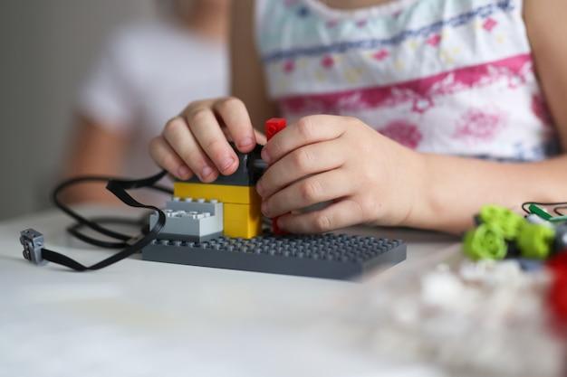 Kid bouwt een robot van ontwerper met behulp van laptop