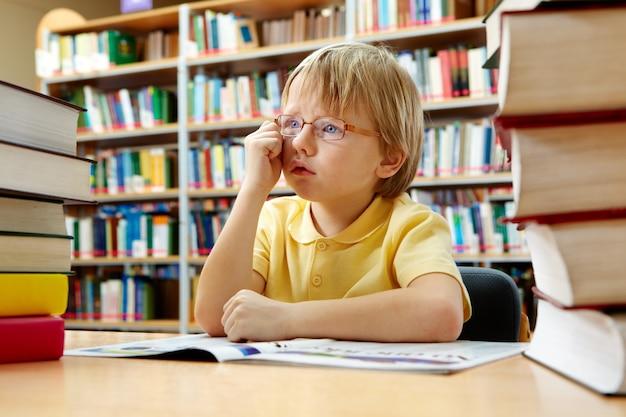 Kid dagdromen in de bibliotheek