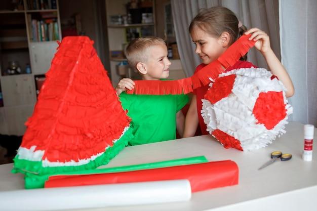 Kid doet pinata met karton uit gebruikte doos en gekleurd papier diy decoratie op verjaardagsfeestje